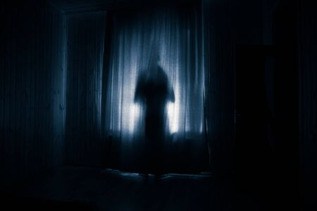 Horror silhouette in window with curtain inside bedroom at night. Horror scene. Halloween concept. Blurred silhouette of ghost Stock Photo - 150115160
