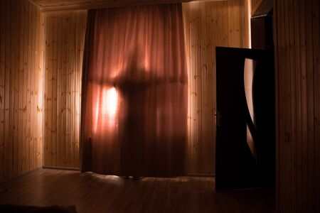 Horror silhouette in window with curtain inside bedroom at night. Horror scene. Halloween concept. Blurred silhouette of ghost Stock Photo - 150115163