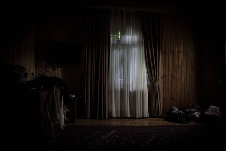 Light in window with curtain inside bedroom at night. Horror scene. Halloween concept. Blurred silhouette of ghost Stock Photo - 150115165