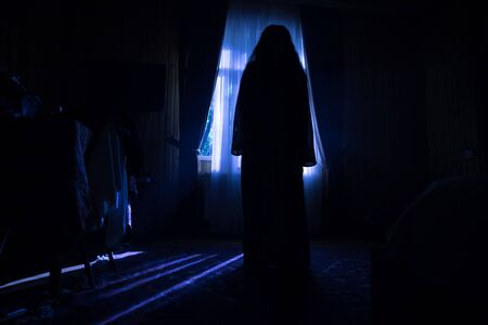 Horror silhouette in window with curtain inside bedroom at night. Horror scene. Halloween concept. Blurred silhouette of ghost Stock Photo - 150115167