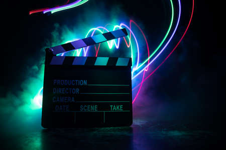 Movie concept. Miniature movie set on dark toned background with fog and empty space. Silhouette of clapboard. Selective focus Stock Photo