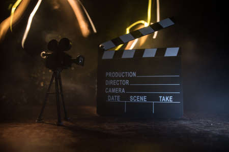 Movie concept. Miniature movie set on dark toned background with fog and empty space. Silhouette of vintage camera on tripod and clapboard. Selective focus Stock Photo