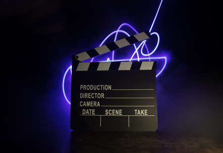 Movie concept. Miniature movie set on dark toned background with fog and empty space. Silhouette of clapboard on dark. Selective focus