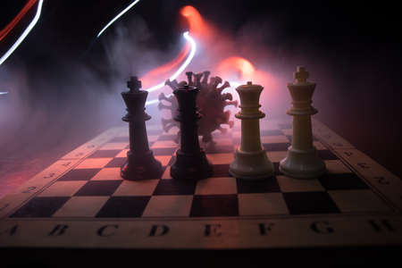 Chess board game concept strategy of business in Covid global pandemic. Big Corona virus miniature model on chessboard with fog and backlight. Creative artwork decoration. Selective focus