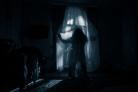 Horror silhouette in window with curtain inside bedroom at night. Horror scene. Halloween concept. Blurred silhouette of ghost Stock Photo