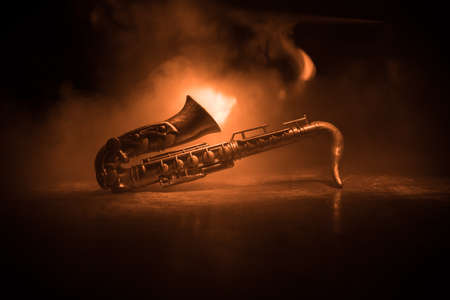 Music concept. Saxophone jazz instrument. Alto gold sax miniature with colorful toned light on foggy background. Saxophone music instrument in lowlight. Selective focus Banque d'images