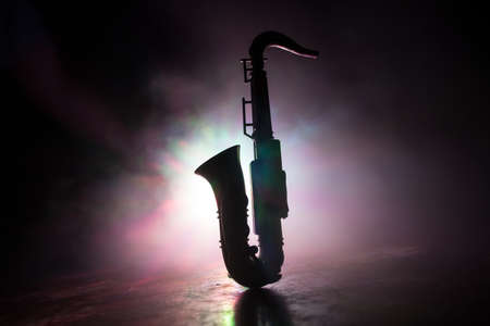 Music concept. Saxophone jazz instrument. Alto gold sax miniature with colorful toned light on foggy background. Saxophone music instrument in lowlight. Selective focus