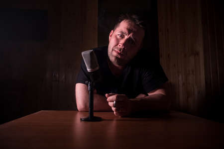 Caucasian man news broadcaster sat at a desk with microphone in dark room. Performer with microphone. Male musician singing into a microphone. Shot on a black background. Dark atmosphere Stock Photo - 152333585