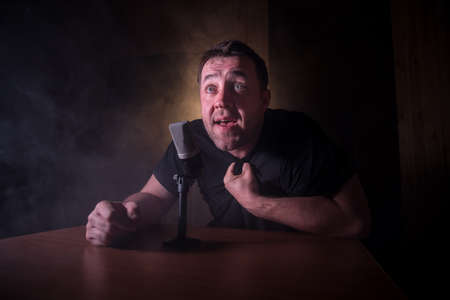 Caucasian man news broadcaster sat at a desk with microphone in dark room. Performer with microphone. Male musician singing into a microphone. Shot on a black background. Dark atmosphere Stock Photo - 152333586