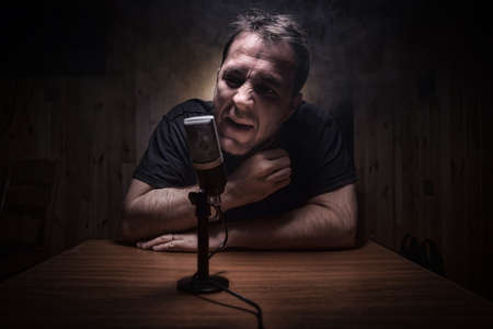 Caucasian man news broadcaster sat at a desk with microphone in dark room. Performer with microphone. Male musician singing into a microphone. Shot on a black background. Dark atmosphere Stockfoto