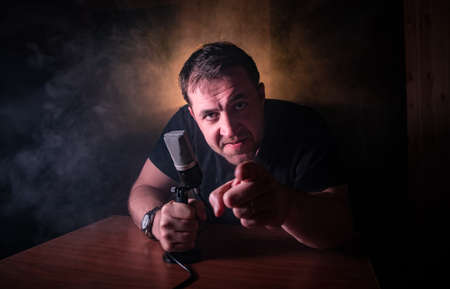 Caucasian man news broadcaster sat at a desk with microphone in dark room. Performer with microphone. Male musician singing into a microphone. Shot on a black background. Dark atmosphere Stock Photo - 152333589