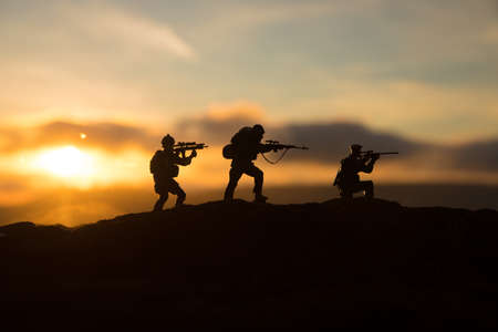 War Concept. Military silhouettes fighting scene on war fog sky background, World War Soldiers Silhouette Below Cloudy Skyline sunset. Selective focus Imagens