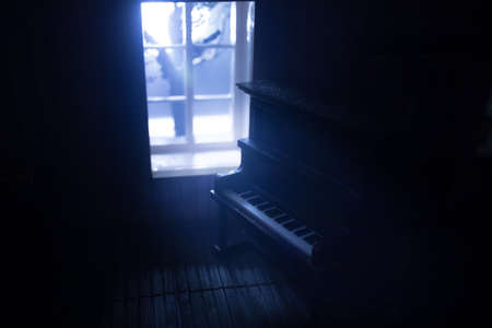 A realistic dollhouse living room with furniture and window at night. Old toy piano in dark room. Selective focus.