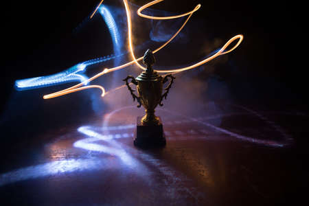 Golden trophy cup on table dark background with copy space. Creative artwork decoration with toned foggy backlight. Selective focus