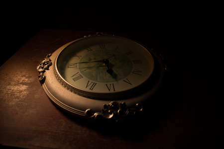 Time concept. Big vintage round clock on wooden table with abstract light. Dark atmosphere. Creative decoration. Selective focus 写真素材