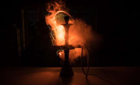 Hookah hot coals on shisha bowl making clouds of steam at dark room. Stylish oriental shisha in dark with backlight. Selective focus