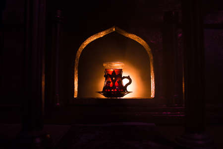 Arabian tea concept. A realistic Arabian interior miniature with window and columns. Arabian tea in glass inside room. Low light lounge interior with carpet. Selective focus