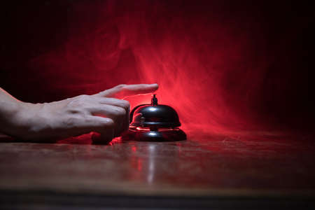 Calling service bell on wooden table with toned lights on dark background. Hotel reception bell, Hand ringing in service bell, selective focus