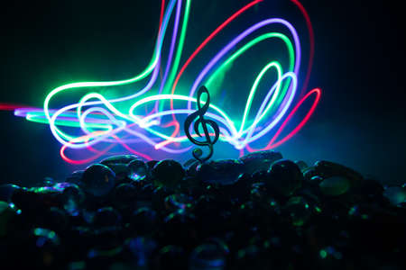 Music concept. Musical symbol treble clef stainless steel miniature with colorful toned light on foggy background. Selective focus