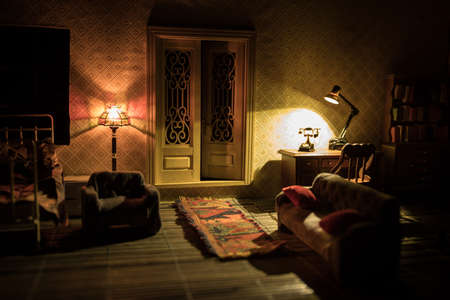 A realistic dollhouse living room with furniture and window at night. Artwork table decoration with handmade realistic dollhouse. Man wathing retro style Television in dark room. Selective focus. 写真素材