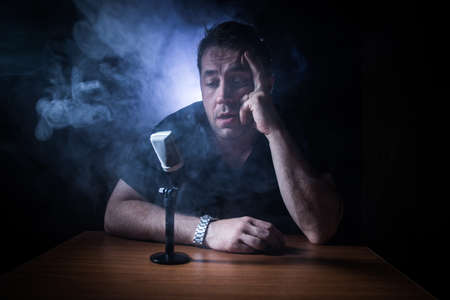 Caucasian man news broadcaster sat at a desk with microphone in dark room. Performer with microphone. Male musician singing into a microphone. Shot on a black background. Dark atmosphere Stock Photo