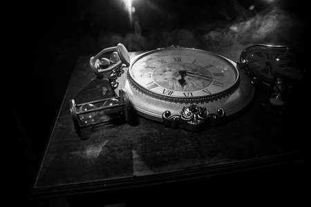 Time concept. Big vintage round clock on wooden table with abstract light. Dark atmosphere. Creative decoration. Selective focus Banque d'images