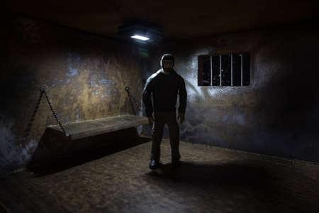 Man in prison man behind bars concept. Old dirty grunge prison miniature. Dark prison interior creative decoration. Selective focus