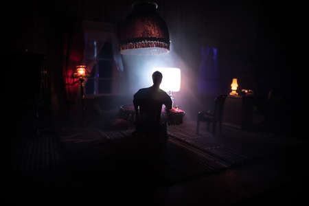 A realistic dollhouse living room with furniture and window at night.