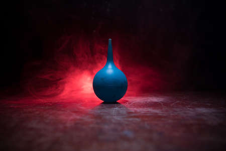 Blue enema on dark background with backlight. Creative artwork decorated with light. Selective focus Stock Photo