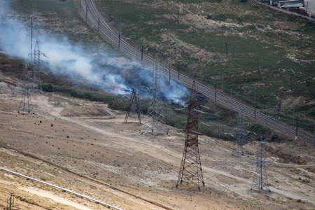 The field burns near railway. Dry grass field on fire. Zoom shot Stock Photo