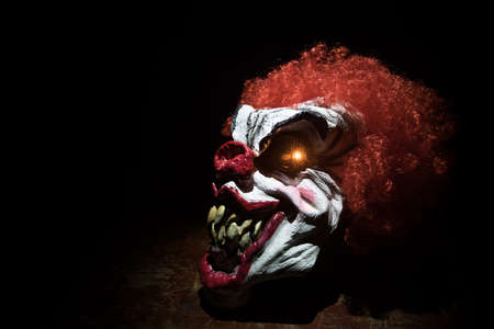 Spooky Clown head on wooden table. Evil clown smiling on dark foggy background. Halloween concept. Selective focus