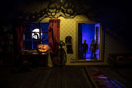 Halloween horror concept with glowing pumpkin. A realistic dollhouse living room with furniture, door and window at night. Scary zombies outside. Selective focus.