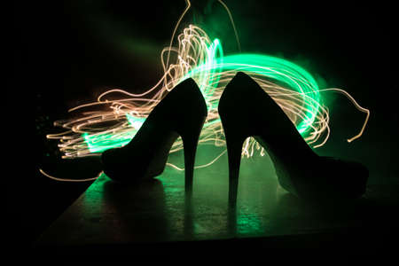 Artwork decoration. Silhouette of a high heel women shoes at dark. Women power or women domination concept. Selective focus