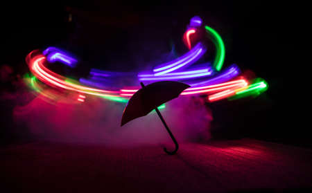 Silhouette of umbrella miniature on table with dark toned foggy background. Creative concept. Selective focus Stock Photo