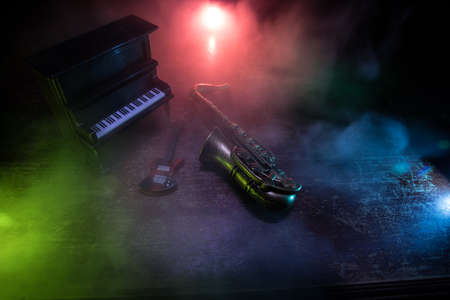 Music concept. Saxophone jazz instrument. Alto gold sax miniature with colorful toned light on foggy background. Musical instruments in lowlight. Selective focus