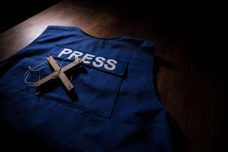 Media Journalism Global Daily News Content Concept. Blue journalist (press) vest in dark with backlight and fog. Magnifier on journalist vest. Selective focus Imagens