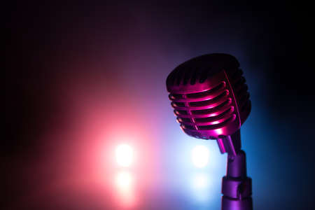 Retro style microphone on background with backlight. Vintage silver Microphone for sound, music, karaoke. Speech broadcast equipment. Live pop, rock musical performance. Selective focus Imagens