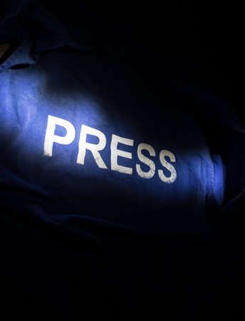 Media Journalism Global Daily News Content Concept. Blue journalist (press) vest in dark with backlight and fog. Selective focus