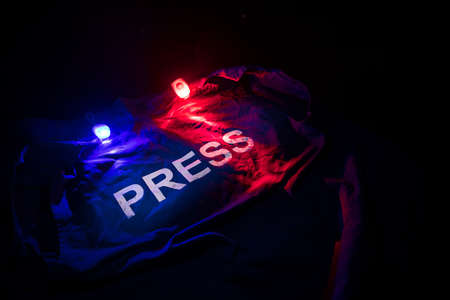 Media Journalism Global Daily News Content Concept. Blue journalist (press) vest in dark with backlight and fog. Police lights red and blue. Selective focus