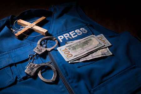 Media Journalism fake news concept. Blue journalist (press) vest in dark with backlight and fog. Puppeteer controls media. Selective focus Banque d'images