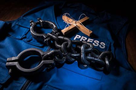 Media Journalism fake news concept. Blue journalist (press) vest in dark with backlight and fog. Dirty money on journalist vest. Selective focus