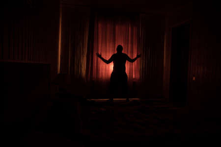 Horror silhouette in window with curtain inside bedroom at night. Horror scene. Halloween concept. Blurred silhouette of ghost