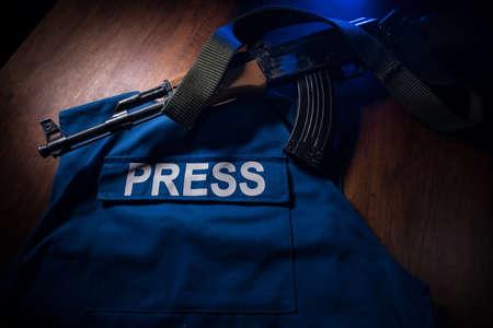 Media Journalism at risk concept. Blue journalist (press) vest in dark with backlight and fog. Weapon on journalist vest. Selective focus