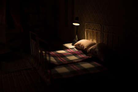 Old vintage single bed at night. A realistic dollhouse bedroom with furniture and window. Selective focus