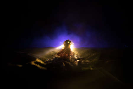 Girl staying on the road in the headlights of a car. Decoration miniature. Horror concept. Selective focus Stock fotó