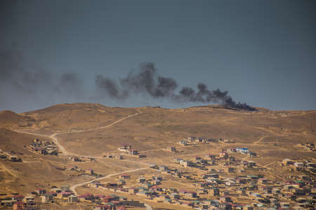 Black smoke and fire on mountain near city. Zoom shot 版權商用圖片
