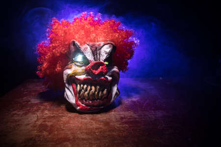 Spooky Clown head on wooden table. Evil clown smiling on dark foggy background. Halloween concept. Selective focus Reklamní fotografie