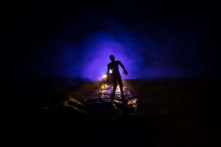 photo of a car stopped on the road lighting up a zombies. Silhouette terrible zombie night near the car. Miniature decoration. Selective focus Stock Photo