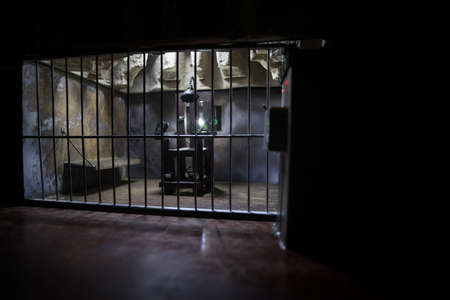 Execution concept. Death penalty electric chair miniature in selective focus inside old prison. Old prison bars cell lock. Creative artwork decoration. Electric chair scale model in the dark