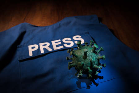 Creative concept of manipulation with media or fake news. The Covid19 miniature on journalist vest. Selective focus